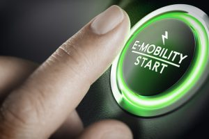 Man_pushing_green_car_button._Concept_of_e-mobility._Composite_image_between_a_hand_photography_and_a_3D_background.