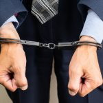 arrested_businessman_in_handcuffs._Businessman_bribetaker_or_briber._Concept_of_fraud,_detention,_crime_and_bribery