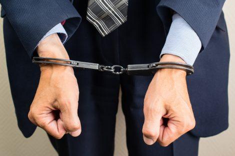 arrested_businessman_in_handcuffs._Businessman_bribetaker_or_briber._Concept_of_fraud,_detention,_crime_and_bribery