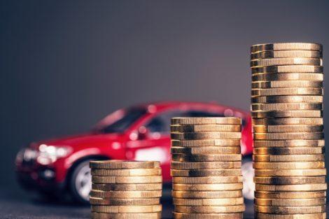 Ansteigende_Stapel_mit_Münzen_und_einem_roten_Auto_im_Hintergrund