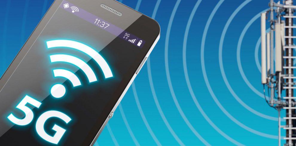 5G-Smartphone vor einem Funkmasten.