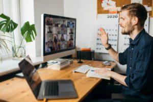 Junger Mann in Zoom Besprechung Desktop PC