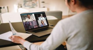 Frau vor Laptop in Videokonferenz