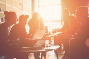 Junge Unternehmer am Tisch im Gegenlicht. Startups wollen sich laut Startup-Report 2020 für mehr Nachhaltigkeit engagieren.