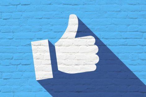 Facebook thumbs up Daumen hoch auf einer Steinmauer
