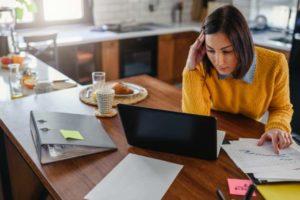 Homeoffice in Zeiten von Corona: Junge Businessfrau sitzt in ihrer zum Homeoffice umgebauten Küche. Bild: lordn via Adobe Stock