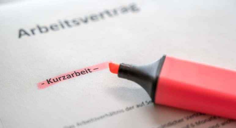 Das Wort Kurzarbeit, rot markiert auf einem Arbeitsvertrag. Die Maßnahme macht Mitarbeiter unzufrieden