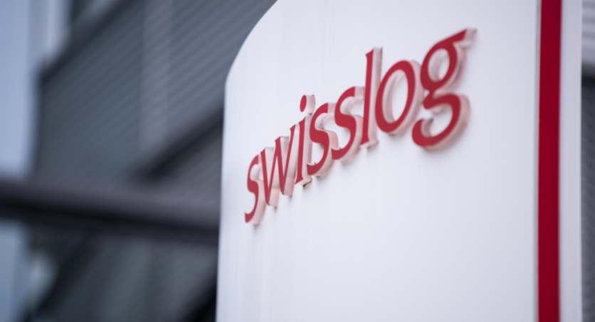 Swisslog-Logo vor Hauptgebäude der AG in der Schweiz