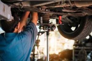 Mechaniker schraubt am Boden eines Autos. Die Autoindustrie hat teils heftige Absatzrückgänge zu beklagen.